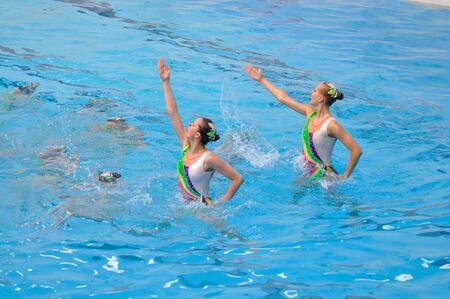 nataci�n sincronizada: Varsovia, Polonia - 12 de junio de 2011: Un equipo de nataci�n sincronizada pantalla en la piscina durante la competici�n en la Universidad de Educaci�n F�sica. Editorial