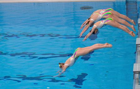 Warschau, Polen - 12 juni 2011: Een synchroonzwemmen team, springt in het water, tijdens de wedstrijd aan de Universiteit van Lichamelijke Opvoeding.