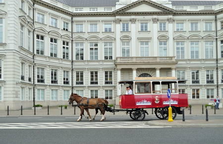 omnibus: Warsaw, Poland - August 10, 2010: Tourist Omnibus horse-drawn tram in front of the Jablonowski palace.