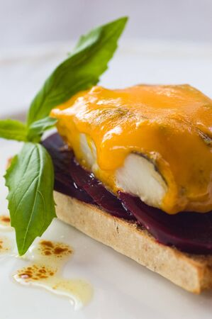Smoked Haddock On A Bed Of Beet-root With Melted Blue Cheese Stock Photo