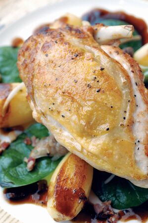 fowl: Roast Guinea Fowl on a bed of gently roasted potato, spinach and diced bacon Stock Photo
