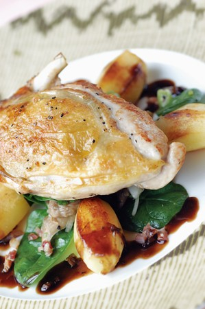 Roast Guinea Fowl on a bed of gently roasted potato, spinach and diced bacon Stock Photo