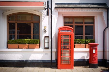 Red telephone box and a red post box outside a white restaurant