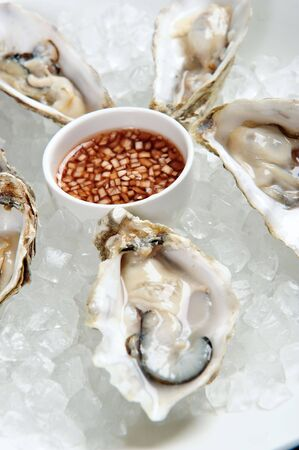 Fresh rock oysters on a bed of ice accompanied by a shallot dressing Stock Photo