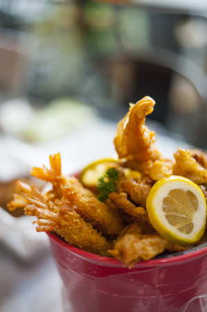 A close-up shot of some golden fried seafood served on a bucket