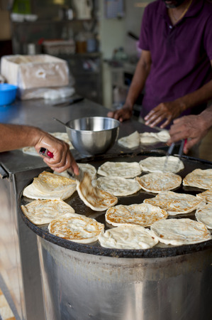 Crop shot of some kitchen helpers frying some India flatbread, called Roti Prata, till they turned crispy and brown Stock Photo