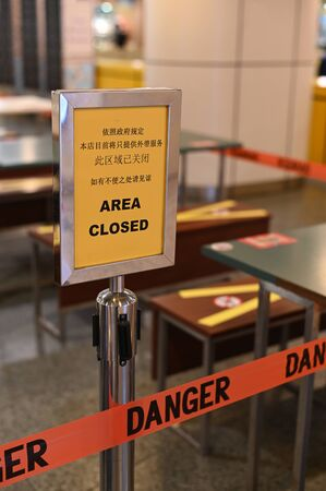 Outdoor eatery placed a closed sign for a pandemic lockdown period, it is in Chinese and English language