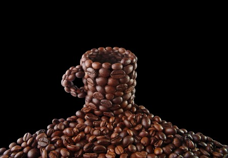 Cup from coffee grains on a black background