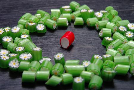 unequal: Muchos caramelos en una superficie de madera. Relaci�n desigual de uno a cien Foto de archivo