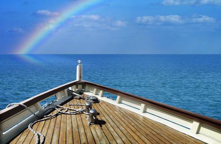 穏やかな海で出荷します。水平線に虹。