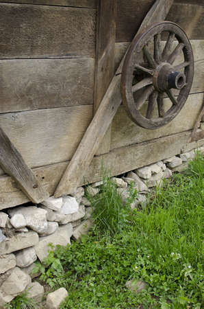 wheel house: Old wooden wheel and traditional house.