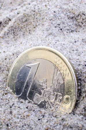 Euro coin macro in sand. photo