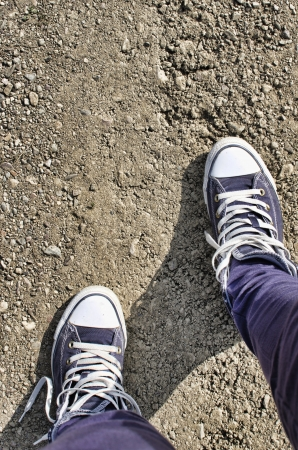 スニーカー: 汚れた道路上 10 代フィート。 写真素材