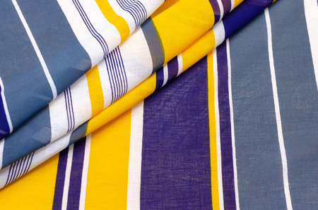 The texture of cotton fabric, batist in blue-white-yellow stripes