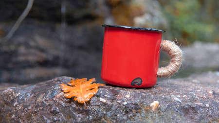 Red watercolor enamel mug cup stay on the rock near water spring. Retro vintage style. Metal cute mug.