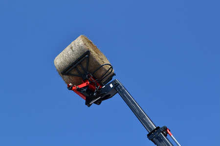 Tractor pick up a round bale in air with blue sky photo