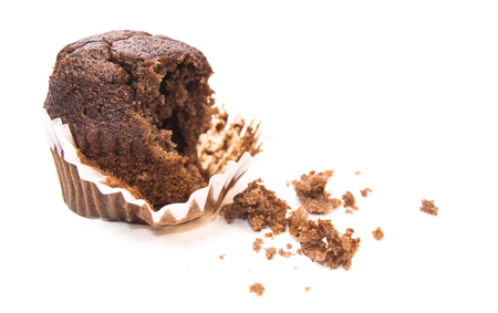 Half-eaten chocolate muffin on a white background