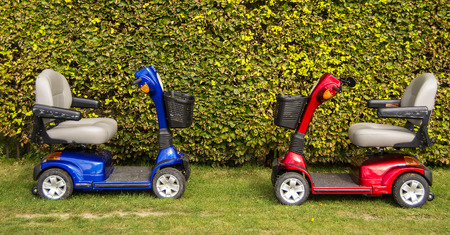 A red and blue mobility scooters on the grass. Foto de archivo
