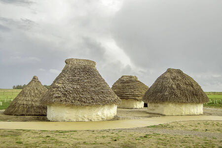 aborigines: Historic old mud huts with straw roofs on the field.