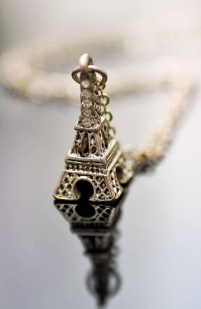 reflective: Eiffel tower charm necklace on a reflective surface.