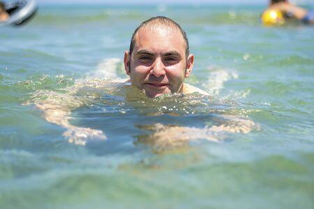 azure: Man swimming in the azure blue sea.