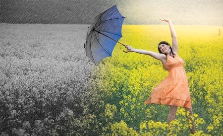 Frau mit Regenschirm gegen sonnigen Platz in einen dunklen, kalten Ort gezogen.