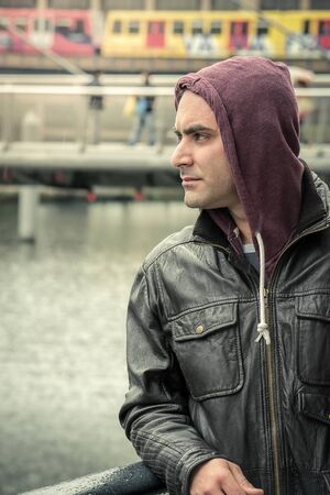 lonely man: Portrait of a lonely man with a hoodie in the city. Stock Photo