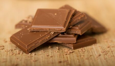caloric: Closeup image of tasty chocolate on a wooden board.