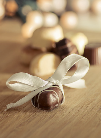 bonbonniere: Chocolate bonbon with a white bow on a wooden table.