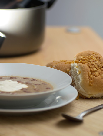 soured: Bean soup with soured cream served with soft rolls. Stock Photo