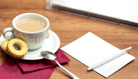 organised: Office table with a folder, cup of tea and a notepad.
