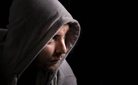 mystery man: Mysterious man in a hoodie against a dark background. Stock Photo