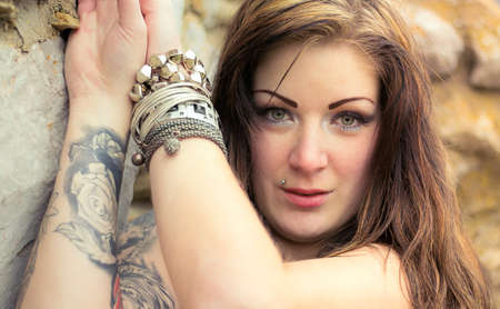 tattoed: Portrait of a beautiful young brunette woman posing near rocks