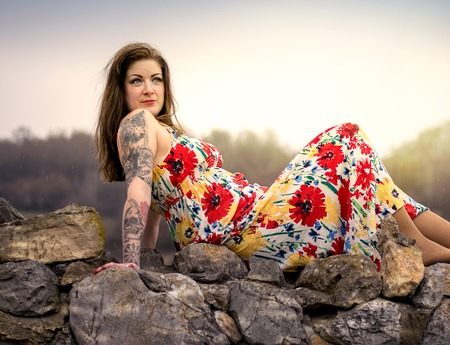 tattoed: Woman in a floral dress posing on a rock Stock Photo