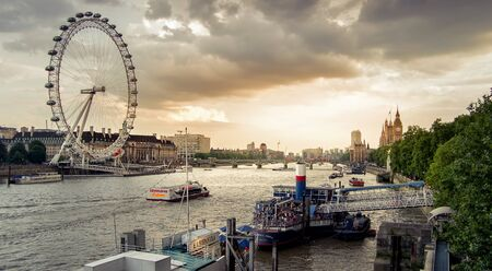 city of westminster: London, England - July 26, 2014 - Sunset in London over the Thames river in Westminster with the London eye and Big ben in the background. London is the capital city of England and a popular tourist destination.