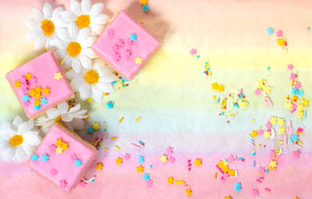 Pink iced cakes with sprinkles on a colourful background
