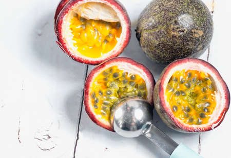 Passion fruit seeds being scooped out with a spoon