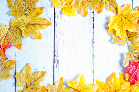 Wooden background framed with colourful autumn leaves