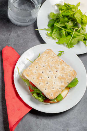 Thin sandwich with cheese and salad on a white plate