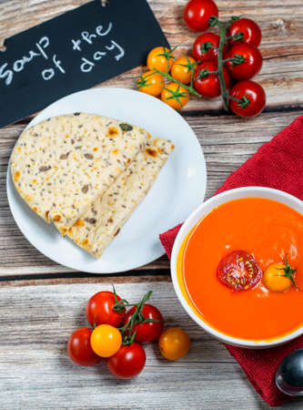Fresh tomato soup served with bread and fresh cherry tomatoes Stock Photo