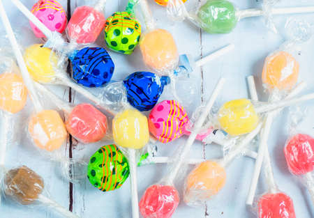 Varrious colourful lollipops on a wooden table.