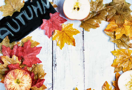 Autumn background with colourful leaves and apples