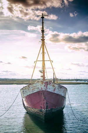 Old rusty boat anchored in the river
