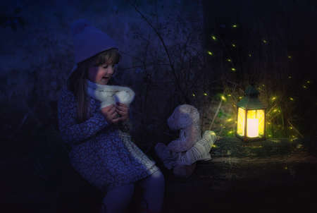 Little girl at night time with a teddy bear in the forest