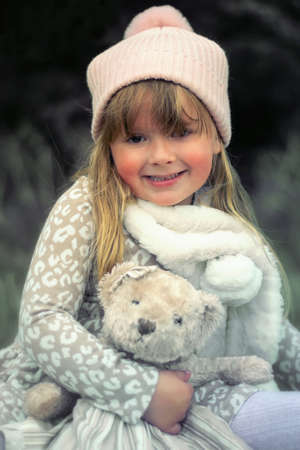 Little girl sitting on a bench with a teddy bear Stock Photo