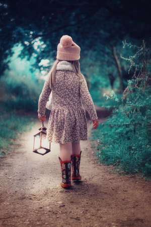 Little girl walking into the forest with a lamp
