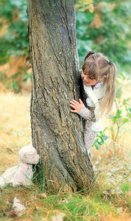 Little girl playing hide and seek with a teddy