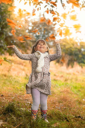 Happy little child playing with leaves at autumn time Stock Photo