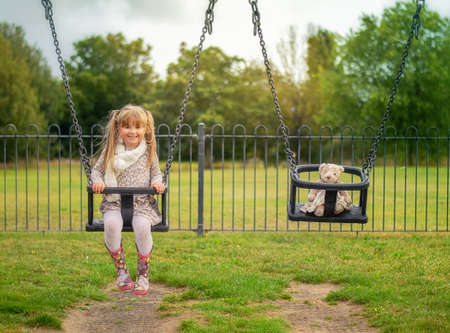 Little girl on the swing with a teddy bear