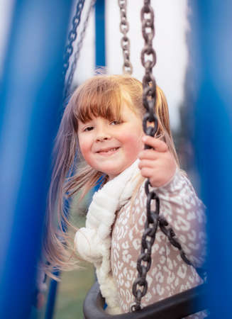 Blonde little girl on the chain swing